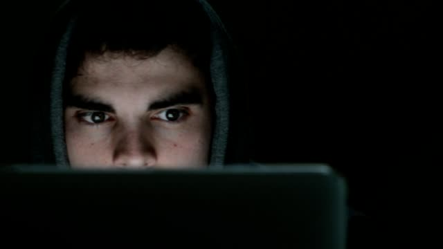 Camera tracks across face of suspicious looking young man wearing hooded top working on laptop at night