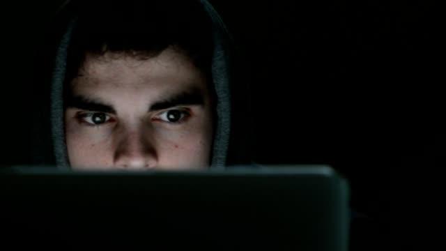 Camera bijgehouden over gezicht van verdacht uitziende jonge man dragen hooded top werken op laptop's nachts