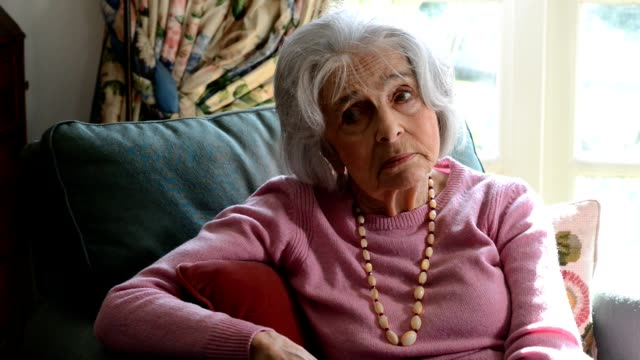 Camera tracks across frame as sad looking senior woman sits in armchair at home