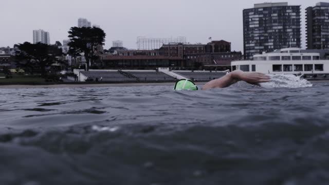 vídeos de stock, filmes e b-roll de camera tracks as senior woman swims in cold, grey san franciso bay with city buildings in background. - touca de natação