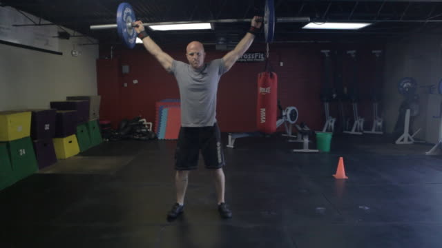 Camera tracks in from wide to close-up as Dustin performs series of snatches.