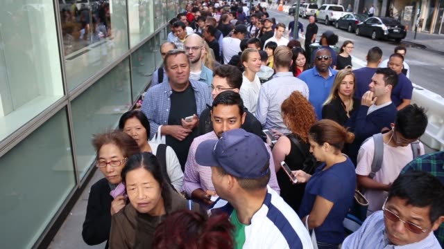camera tracks line of people waiting outside and entering the apple store at 5th ave and 58th street in midtown manhattan during launch of iphone 8... - stå i kö bildbanksvideor och videomaterial från bakom kulisserna