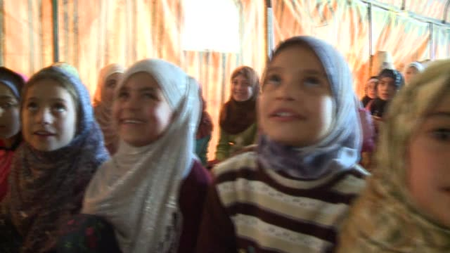 Camera tracks past young Syrian Civil War refugees in mosque in Internal Displaced Persons' camp in Syria