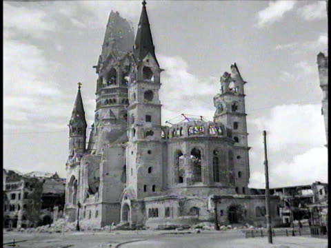 stockvideo's en b-roll-footage met camera travels up demolished street approaching a cathedral / berlin germany - puin