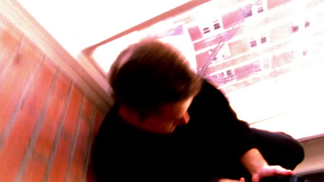 shaky high contrast ms camera turning around man using pda by window in empty loft apartment - high contrast stock videos & royalty-free footage