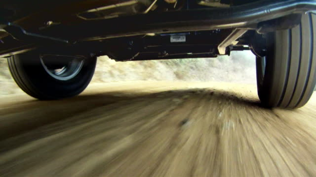 camera under jeep looking at wheels and axel on dirt road - strada in terra battuta video stock e b–roll