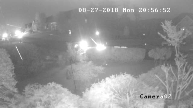 CCTV camera view of spider web and car driving at night
