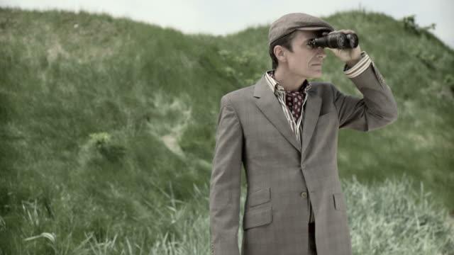 stockvideo's en b-roll-footage met camera zooming in on man using binoculars - verrekijker