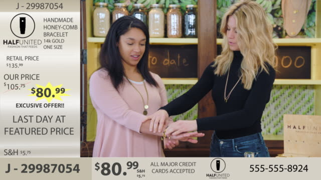 stockvideo's en b-roll-footage met camera zooms in as two women discuss and try on bracelets in modern jewelry infomercial. - advertentie