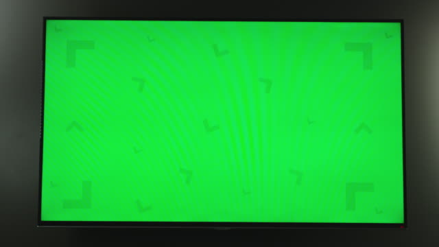 camera zooms in toward a flatscreen tv monitor hanging on a wall with green screen and tracking markers for screen replacement. - gerätebildschirm stock-videos und b-roll-filmmaterial