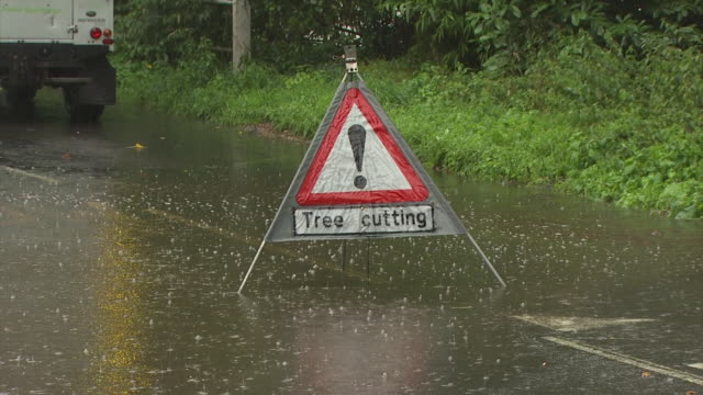 stockvideo's en b-roll-footage met camera zooms out from tree cutting sign to reveal electricity company vans in heavy rain on flooded road with tree down across road and power cables down. england, uk - stroomuitval