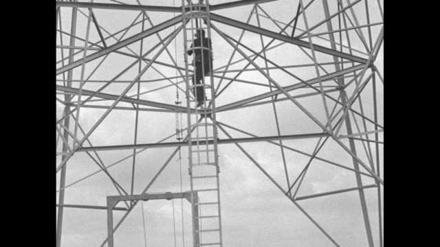 cameraman climbing ladder of radio tower / man waving from high up tower he continues climbing / looking straight up at man waving atop tower /... - mast stock videos & royalty-free footage