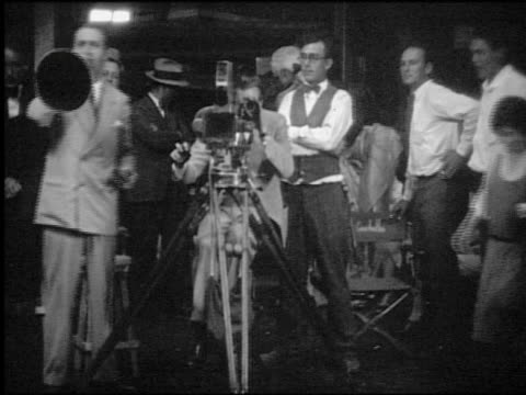 b/w cameraman cranking camera while director shouts through megaphone / rest of film crew in background - film director stock videos & royalty-free footage