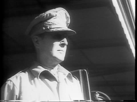 Cameraman Edouard Genock at his desk speaking to the camera / troops lined up in formation at a train station a train arrives at the station / a...
