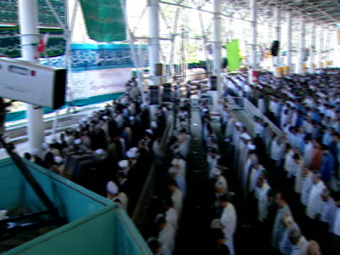 pan cameraman filming congregation of worshipers standing during midday prayer / qom iran - midday stock videos and b-roll footage