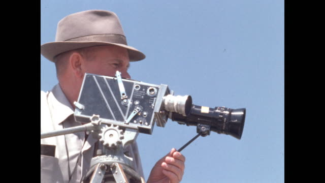 stockvideo's en b-roll-footage met cameraman in hat operates 16mm movie camera - cameraman