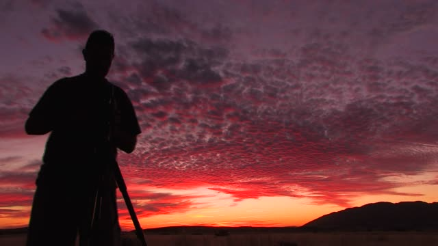A cameraman in silhouette films a purple and orange sky in Namibia at sunset. Available in HD.