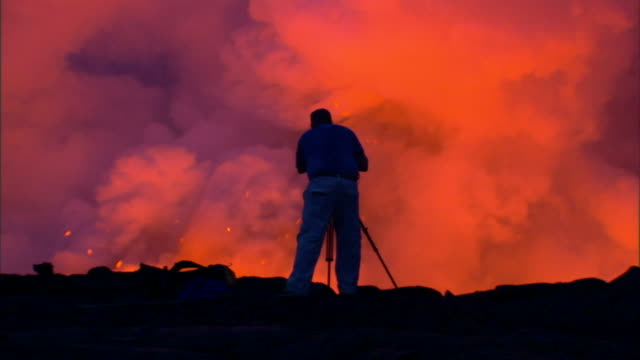 a cameraman looks through a camera as a volcano erupts in front of him. - cinematographer stock videos & royalty-free footage