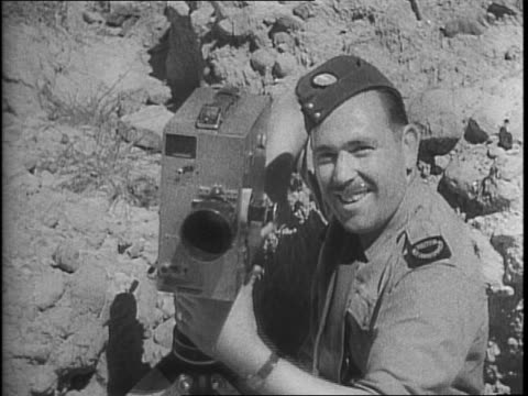 cameraman maurice ford poses with camera in uniform / birds flock in front of a temple in rangoon / rooftop of the temple / view of temple moves to... - wrack stock-videos und b-roll-filmmaterial