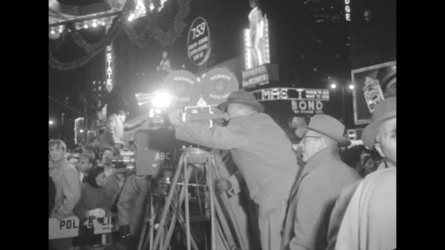 Cameraman operates film camera outside the theater see spectators behind barricade on sidewalk and neon marquees in background