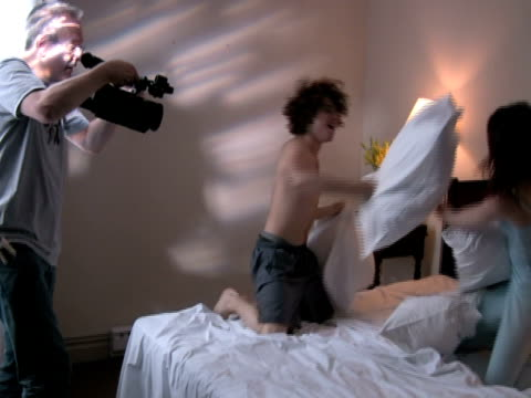 cameraman shooting young couple pillow-fighting - human relationship stock videos and b-roll footage