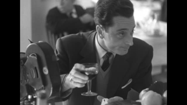 cameraman sitting at table drinking glass of wine waiting for arrival of farouk, his camera sitting on table next to him / note: exact year not known - esilio video stock e b–roll