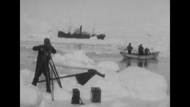 VS cameraman stands on ice floe with his movie camera on tripod as he shoots film small boat stands behind him and Richard E Byrd's ship SS Chantier...