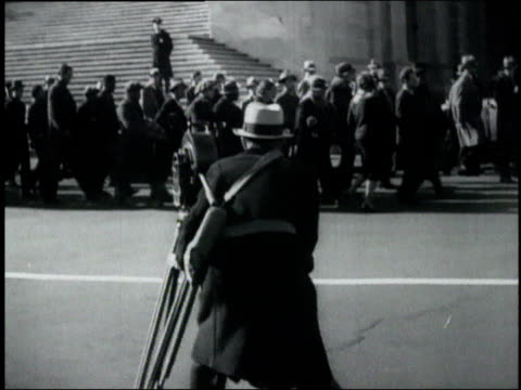ts cameraman with camera on tripod filming crowd marching past pedestrian ducking away / washington district of columbia united states - 1932 stock-videos und b-roll-filmmaterial