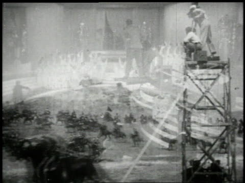 vídeos de stock e filmes b-roll de 1951 montage cameramen filming indoors on a sound stage and outdoors with a tracking dolly following galloping horses - montagem de filme estúdio de cinema