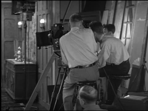 B/W REAR VIEW PAN cameramen on dolly moving toward people sitting at dining room table on set
