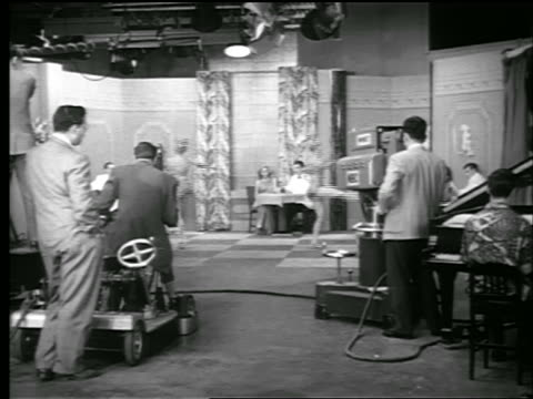 vídeos de stock, filmes e b-roll de b/w 1948 rear view tv cameramen shooting 2 women dancing in tv studio - câmera de televisão