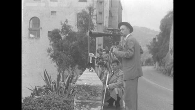 cameramen stake out the villa iberia far in the distance below / villa iberia, saint jean cap ferrat, france / watchful cameramen at the side of a... - cote d'azur stock videos & royalty-free footage