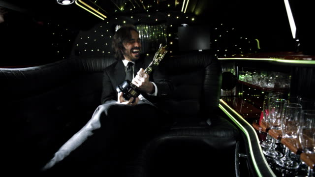 Cameras flash as excited celeb cheers with awards trophy in backseat of limousine at awards show