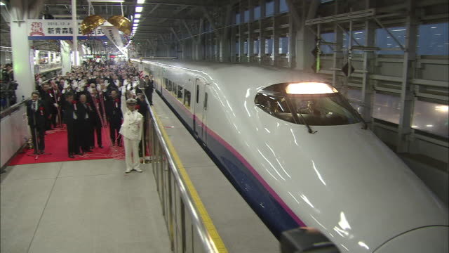 Cameras flash as journalists railway officials and spectators watch the first departure of the new model Hayate Number 12 at Aomori Station Japan