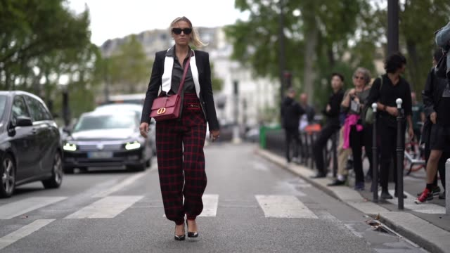 stockvideo's en b-roll-footage met camila carril wears sunglasses, a black and white blazer jacket, a red bag, red and black checked print large pants, black high heeled shoes, outside... - blazer