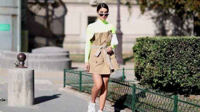 Camila Coelho wearing white asymmetric sneakers brown belted off shoulder dress neon turtleneck long shirt seen outside Maison Margiela during Paris...