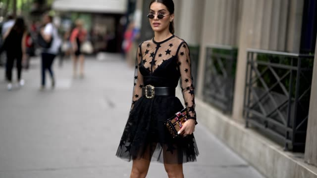 Camila Coelho wears a black lace mesh dress with stars a belt and a Vuitton clutch outside the Elie Saab show during Paris Fashion Week Haute Couture...