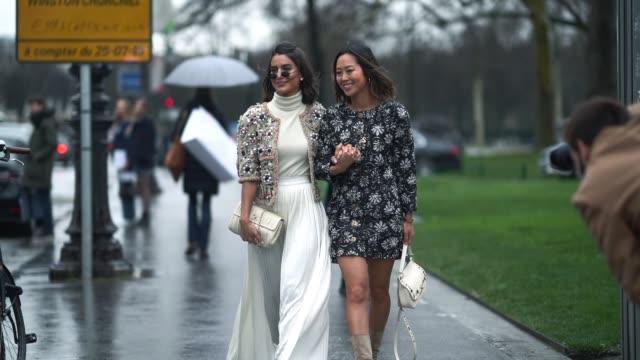 Camila Coelho wears a Chanel jacket a white dress a Chanel bag Aimee Song wears a flower print dress boots outside Chanel during Paris Fashion Week...