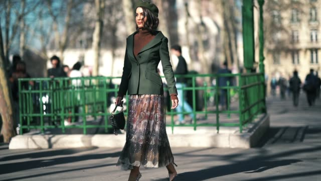 camila coelho wears a green beret hat, a green blazer jacket, a brown wool turtleneck pullover, a dior monogram saddle bag, a colored pleated skirt,... - dolcevita video stock e b–roll