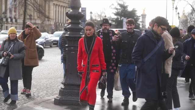 camila coelho wears earrings, a black turtleneck pullover, a red long wool jacket with buttons and pockets, a tweed checked colored chanel bag, black... - fashion week stock videos & royalty-free footage