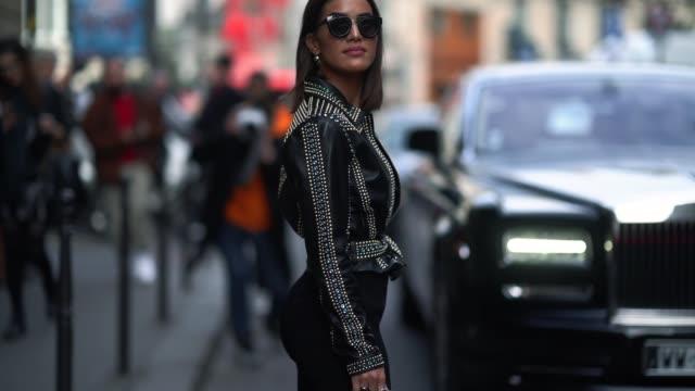 vídeos y material grabado en eventos de stock de camila coelho wears sunglasses, a balck leather jacket, a white t-shirt, black pants, blue shoes, outside elie saab, during paris fashion week -... - camisa blanca