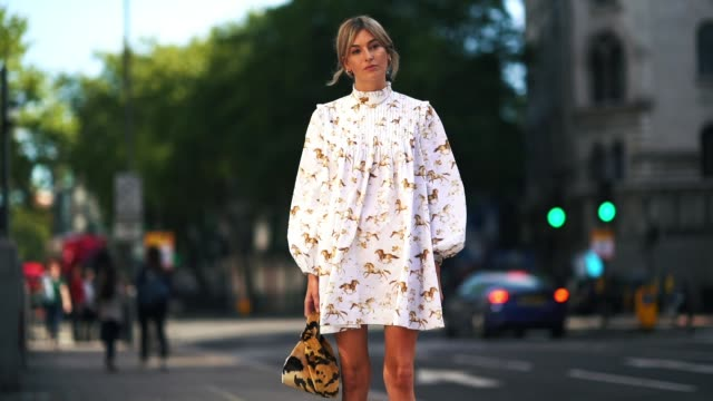 vidéos et rushes de camille charriere wears a white dress with printed features, a leopard print bag, boots, during london fashion week september 2018 on september 15,... - bottes