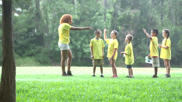 camp counselor with children in park walking single file - summer camp helper stock videos & royalty-free footage