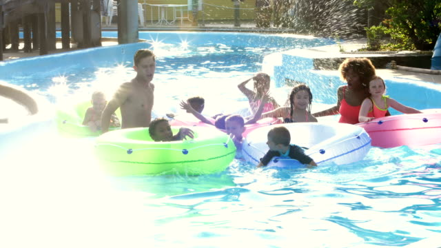 camp counselors, children at water park on lazy river - summer camp helper stock videos & royalty-free footage