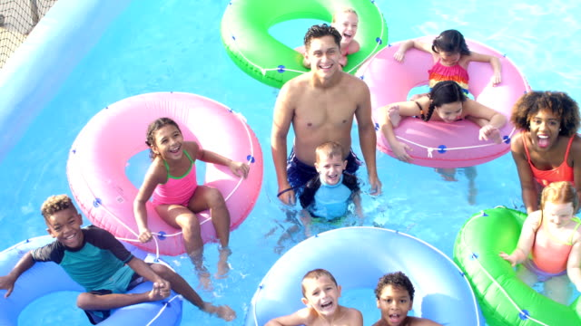 camp counselors, children at water park on lazy river - inner tube stock videos and b-roll footage