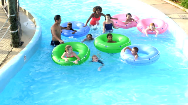 camp counselors, children at water park on lazy river - rubber ring stock videos & royalty-free footage