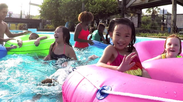 Camp counselors, children at water park on lazy river