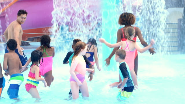 Camp counselors with multi-ethnic children at water park