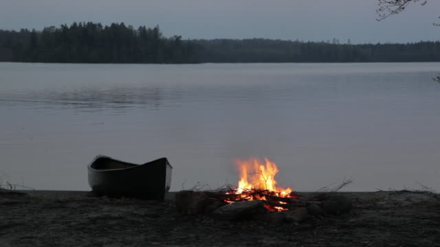 ws pan camp fire and canoe by side of lake / copenhagen, sjaelland, denmark - camp fire stock videos & royalty-free footage