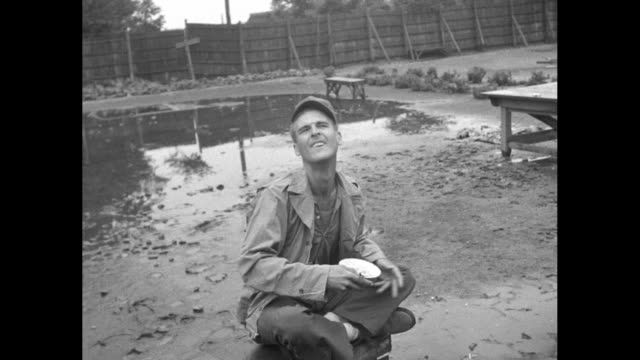 vídeos de stock, filmes e b-roll de ls camp perimeter with soldiers / fs soldier eats rice from bowl then spits it out and throws bowl / cu interior camp cell / cu camp cell interior /... - prisioneiro de guerra